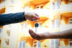 Concept of buying, selling and renting housing. A woman`s hand p. Asses the keys to the man`s hand from the apartment or house, against the backdrop of a Royalty Free Stock Image