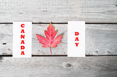 Concept Canada Day. With red maple leaf on vintage wooden table Stock Photography