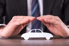 Concept of car insurance. With hands over a car Stock Photos