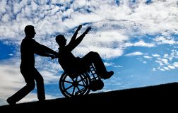 Concept of care and disability. Happy disabled person in a wheelchair having a great time with the family. The concept of care and disability Stock Image