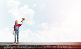Concept of careless happy childhood with girl dreaming to become pilot royalty free stock images
