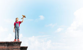Concept of careless happy childhood with girl dreaming to become pilot royalty free stock photo