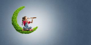 Concept of careless happy childhood with girl on green moon Stock Photography