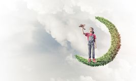 Concept of careless happy childhood with girl on green moon royalty free stock photos