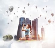 Concept of careless happy childhood with girl looking in future. Cute kid girl on city floating island looking in binoculars royalty free stock image