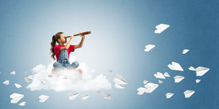 Concept of careless happy childhood with girl looking in spyglass Royalty Free Stock Photo