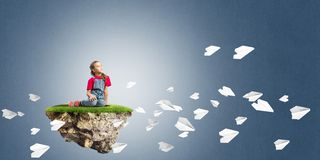 Concept of careless happy childhood with girl and paper planes flying around Royalty Free Stock Photography