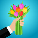 Concept of celebration. Bouquet of beautiful flowers. Business man hand holding out a bunch of tulips. Flat design, vector illustration Royalty Free Illustration