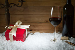 Concept of celebration with gift box, wine glass on snow Stock Images