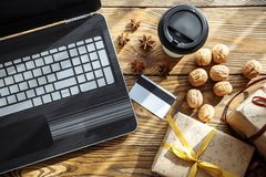 The concept of the celebration, new year, online shopping and technology. A laptop, Bank card, gift boxes and coffee on a wooden table Stock Photos