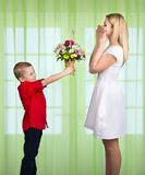 Son gives his beloved mother a beautiful bouquet of tulips.The concept of the celebration,women`s day. The concept of the celebration,women`s day.Son gives his royalty free stock photography