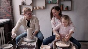 Happy family making earthenware objects in workshop studio. Concept of ceramic art and hobby. Happy family of three people making potter and using electric wheel stock video footage