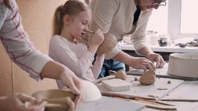 Two adult ceramist person and little girl making earthenware obj. Concept of ceramic art and hobby. Little busy and focused ceramist girl standing near her stock video