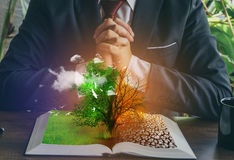 Concept of changes. Open book. One side full of grass with a life tree, different side is desert with a dead tree.cl stock images