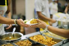 Concept charity for homeless with volunteers donating feeding free food.  royalty free stock images