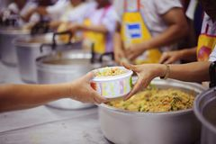 Concept charity for homeless with volunteers donating feeding free food.  stock photos