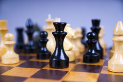 Concept with chess pieces on a wooden chess board Royalty Free Stock Images