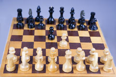 Concept with chess pieces on a wooden chess board Royalty Free Stock Photo