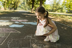 Concept of child imagination. Little girl drawing on asphalt  with chalk Stock Photography