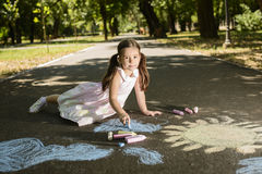 Concept of child imagination. Little girl drawing on asphalt with chalk in a sunny summer day Royalty Free Stock Photos