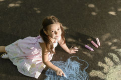 Concept of child imagination. Little girl drawing on asphalt with chalk in a sunny summer day Stock Photography