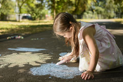 Concept of child imagination. Little girl drawing on asphalt with chalk in a sunny summer day Stock Image
