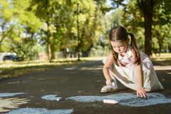 Concept of child imagination. Little girl drawing on asphalt with chalk in a sunny summer day Stock Photo
