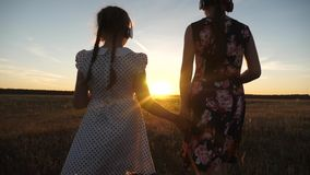 Concept of childhood. Happy teenage girls travel through the park listening to music in the beautiful sunset. children