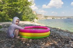 Little boy sitting on the seashore and playing in the inflatable pool on the background of a picturesque landscape. Royalty Free Stock Image
