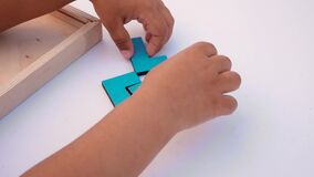 Concept of children`s education. Closeup Slow motion. Hand holding piece of wooden block puzzle. Concept of complex and