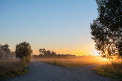 Concept of choice the correct way. Beautiful landscape with sunrise over crossroads spliting in two ways. Rural crossroads on sunset background stock photography