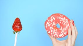 Concept of choice between donut and strawberry. female hands with red nail polish hold with pink donut and strawberry on royalty free stock photos