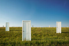The concept of choice. Many doors in a green field royalty free stock image