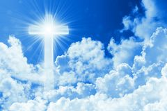Concept of christian religion shining cross on the background of cloudy sky. Sky with cross and beautiful cloud. Divine shining. Heaven, light. Peaceful stock image