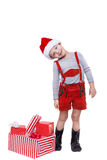 Concept: Christmas in childhood. Kid in red costume of dwarf with gifts Stock Photo