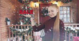 The concept of Christmas discount. Pretty female with long red hair shows her hand a symbol of the sale in snowy weather on the background of of New Year`s stock video