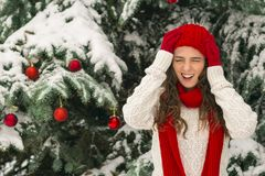 The concept of Christmas and the new year. Winter vibes. The girl in the red and gloves hat near the festive Christmas tree. Copy space. Portrait royalty free stock photography