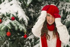 The concept of Christmas and the new year. Winter vibes. The girl in the red and gloves hat near the festive Christmas tree. Copy space. Portrait royalty free stock image