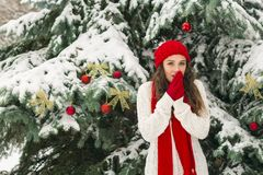 The concept of Christmas and the new year. Winter vibes. The girl in the red and gloves hat near the festive Christmas tree. Copy space. Portrait stock photography