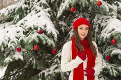 The concept of Christmas and the new year. Winter vibes. The girl in the red and gloves hat near the festive Christmas tree. Copy space. Portrait stock images