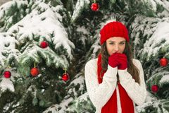 The concept of Christmas and the new year. Winter vibes. The girl in the red and gloves hat near the festive Christmas tree. Copy space. Portrait stock photo