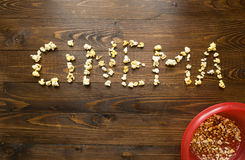 Concept of cinema. Cinema spelled with popcorn over wooden backg Royalty Free Stock Photos