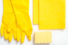 concept cleaning, on a yellow background pink gloves c soft dust brush, melamine sponge and spray for glasses stock photography