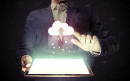 Concept of cloud storage service. Man touches to the cloud icon. He holds tablet pc, that contains a many different online services royalty free stock images