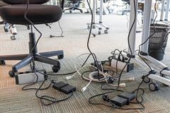 Concept of clutter in office. Unwound and tangled electrical wires under the table. 5S system of lean manufacturing. stock photo