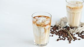 Concept of coffee and cocktails. Cream poured into coffee with ice