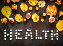 Concept of cold autumn - pills, leaves on dark wood Stock Image