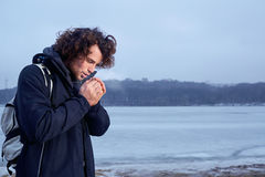 The concept of cold, frost. Curly haired young man warming his Stock Images