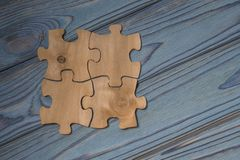 Concept of collected pieces of puzzles on the wood texture background. Idea: Cooperation, strategy, teamwork. Copy space for design Royalty Free Stock Image