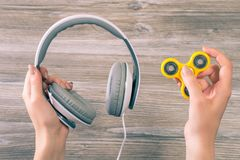 Concept of combining listening to music and using popular fidget spinner. Close up photo of hands holding headphones and fidget sp. Inner over grey wooden royalty free stock photo